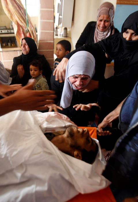 The mother of Palestinian Ahmed Al- Nabahin, 23, grieves over his body during his funeral in the Bureij refugee camp, central Gaza Strip, Monday, Nov. 5, 2012. A Palestinian hospital official says Israeli forces have shot and killed a man at the border fence with the Gaza Strip. It wasn't immediately clear if the man was a civilian. The area is frequently used by militants to fire rockets at nearby Jewish communities, but sometimes others like the mentally disabled enter the area, not understanding its dangers. Photo by Wafa
