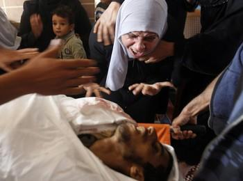 The mother of Palestinian Ahmed Al- Nabahin, 23, grieves over his body during his funeral in the Bureij refugee camp, central Gaza Strip, Monday, Nov. 5, 2012. A Palestinian hospital official says Israeli forces have shot and killed a man at the border fence with the Gaza Strip. It wasn't immediately clear if the man was a civilian. The area is frequently used by militants to fire rockets at nearby Jewish communities, but sometimes others like the mentally disabled enter the area, not understanding its dangers. (AP Photo/Hatem Moussa) AP