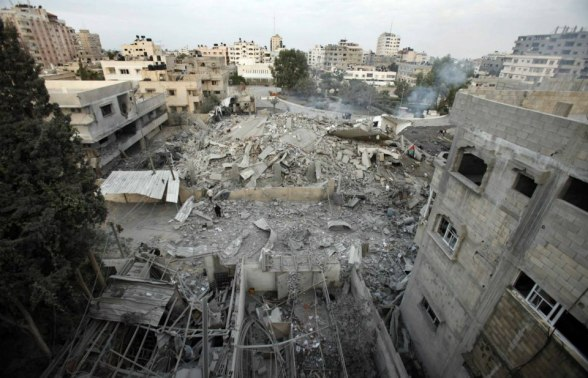 Palestinians inspect the destroyed office building of Hamas Prime Minister Ismail Haniyeh in Gaza City November 17, 2012. Israeli aircraft pounded Hamas government buildings in Gaza on Saturday, including the building housing the prime minister's office, after Israel's Cabinet authorised the mobilisation of up to 75,000 reservists, preparing the ground for a possible invasion into Gaza.