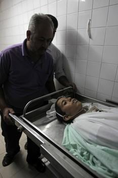The body of Hmeid Abu Daqqa, 13, is pictured at the morgue of a hospital in Khan Yunis, in the southern Gaza Strip on November 8, 2012. Daqqa died after being hit by bullets fired from an Israeli helicopter in the Gaza Strip, a medical official told AFP. AFP PHOTO/ SAID KHATIB