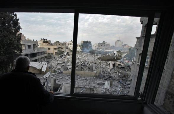 A Palestinian looks from his damaged house at the destroyed office building of Hamas Prime Minister Ismail Haniyeh after Israeli air strikes in Gaza City November 17, 2012. Israeli aircraft pounded Hamas government buildings in Gaza on Saturday, including the building housing the prime minister's office, after Israel's Cabinet authorised the mobilisation of up to 75,000 reservists, preparing the ground for a possible invasion into Gaza. REUTERS/Suhaib Salem