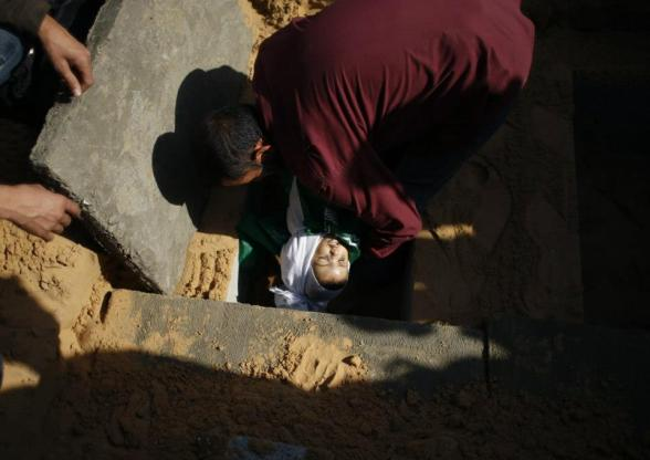 "A man buries a Palestinian child from Abu Sefan family at a cemetery in the northern Gaza Strip November 18, 2012. Two children Jumana Abu Sefan, 18 months old, and her brother Tamer, three and a half years old, were killed in an Israeli air strike on Sunday, hospital officials said. Israel bombed militant targets in Gaza for a fifth straight day on Sunday, launching aerial and naval attacks as its military prepared for a possible ground invasion, though Egypt saw ""some indications"" of a truce ahead. REUTERS/Mohammed Salem"