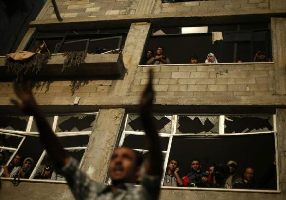 A Palestinian man reacts at the scene of an Israeli air strike on a house in Gaza City November 18, 2012. Ten Palestinian civilians were killed on Sunday in an Israeli air strike on a house in Gaza, Palestinian medics said, the highest civilian death toll in a single incident during five days of fighting. REUTERS/Suhaib Salem (GAZA - Tags: MILITARY CONFLICT) — with Jessica Love.