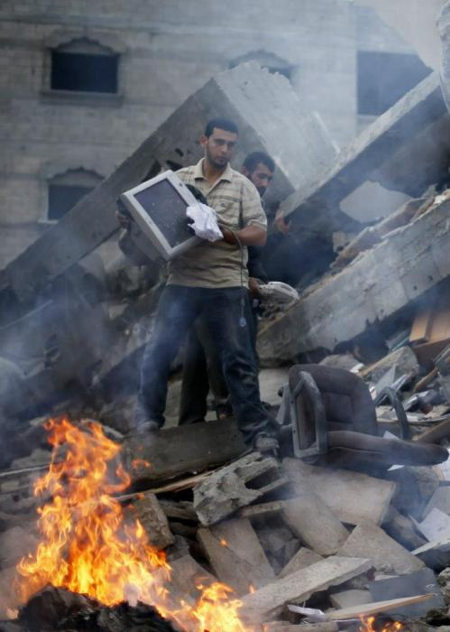 Palestinians inspect the destroyed office building of Hamas Prime Minister Ismail Haniyeh in Gaza City November 17, 2012. Israeli aircraft pounded Hamas government buildings in Gaza on Saturday, including the building housing the prime minister's office, after Israel's Cabinet authorised the mobilisation of up to 75,000 reservists, preparing the ground for a possible invasion into Gaza