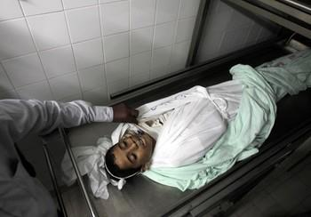 A Palestinian medical examiner uncovers the body of Hmeid Abu Daqqa, 13, at the morgue of a hospital in Khan Yunis, in the southern Gaza Strip on November 8, 2012. Daqqa died after being hit by bullets fired from an Israeli helicopter in the Gaza Strip, a medical official told AFP. AFP PHOTO/ SAID KHATIB