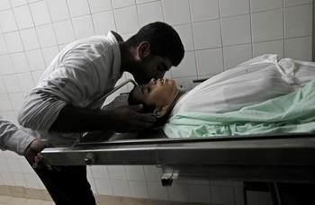 A Palestinian relative of Hmeid Abu Daqqa, 13, bids him farewell at the morgue of a hospital in Khan Yunis, in the southern Gaza Strip on November 8, 2012. Daqqa died after being hit by bullets fired from an Israeli helicopter in the Gaza Strip, a medical official told AFP. AFP PHOTO/ SAID KHATIB