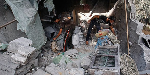 Palestinians look through their belongings in a house destroyed overnight by an Israeli airstrike in Beit Lahiya, northern Gaza Strip, on Sunday. (Photo: AP)