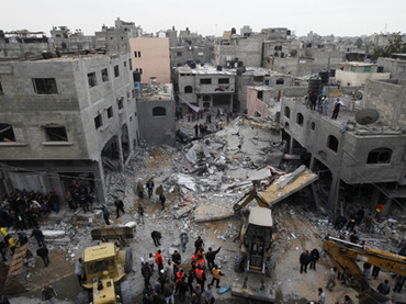 Palestinians gather at the site of an Israeli air raid in Gaza City on November 17, 2012. Israeli air strikes hit the cabinet headquarters of Gaza's Hamas government after militants fired rockets at Jerusalem and Tel Aviv as Israel called up thousands more reservists in readiness for a potential ground war. AFP PHOTO / MOHAMMED ABED