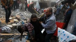 A Palestinian man carries the dead body of a child from the al-Dallu family out from the rubble after an Israeli missile struck a family home, killing at least seven members of the family in Gaza City on November 18, 2012.