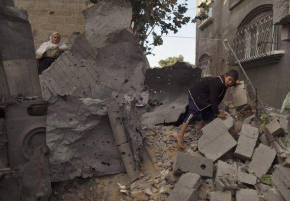 A boy walks amidst rubble of, what Palestinians say, is a house damaged in an Israeli air strike in Jabalya, in the northern Gaza Strip November 11, 2012. An Israeli air strike killed a Palestinian militant in the Hamas-governed Gaza Strip on Sunday as a surge in cross-border violence entered its second day, local officials said. The Israeli military confirmed carrying out an air strike in the area. REUTERS/Mohammed Salem
