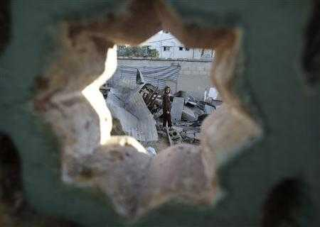A boy looks at what Palestinians say is a house damaged in an Israeli air strike in Gaza City November 11, 2012. REUTERS/Ibraheem Abu Mustafa