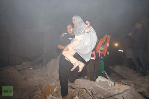 "A Palestinian man evacuates a woman following Israeli air strikes in Gaza City November 14, 2012. Israel launched a major offensive against Palestinian militants in Gaza on Wednesday, killing the military commander of Hamas in an air strike and threatening an invasion of the enclave that the Islamist group vowed would ""open the gates of hell"". REUTERS/Ahmed Zakot"
