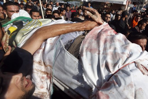 Palestinian holds the hand of Ahmed Al-Jaabari, Hamas's military mastermind, during his funeral in Gaza City November 15, 2012. Hamas fired dozens of rockets into southern Israel on Thursday, killing three people, and Israel launched numerous air strikes across the Gaza Strip, threatening a wider offensive to halt repeated Palestinian salvoes. Israel on Wednesday assassinated Ahmed Al-Jaabari and shelled the enclave from the land, sea and air, killing 13 people, including five militants, three children and a pregnant woman. REUTERS/Mohammed Salem