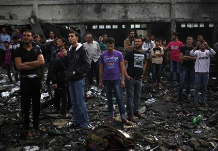 "Palestinians gather around a destroyed house after an Israeli air strike in Gaza City November 18, 2012. Israel bombed militant targets in Gaza for a fifth straight day on Sunday, launching aerial and naval attacks as its military prepared for a possible ground invasion, though Egypt saw ""some indications"" of a truce ahead. REUTERS/Ahmed Jadallah"