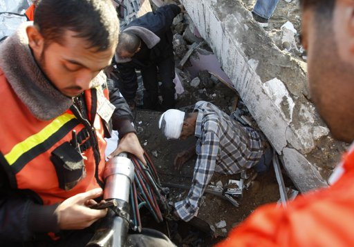 "Palestinian members of civil defense help evacuate a wounded man under the rubble of his house, after an Israeli air strike in Gaza City November 18, 2012. Israel bombed militant targets in Gaza for a fifth straight day on Sunday, launching aerial and naval attacks as its military prepared for a possible ground invasion, though Egypt saw ""some indications"" of a truce ahead. REUTERS/Ahmed Zakot"