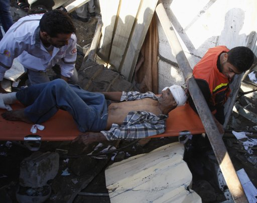 "Palestinians carry a wounded man after being evacuated from under the rubble of his house, following an Israeli air strike in Gaza City November 18, 2012. Israel bombed militant targets in Gaza for a fifth straight day on Sunday, launching aerial and naval attacks as its military prepared for a possible ground invasion, though Egypt saw ""some indications"" of a truce ahead. REUTERS/Ahmed Zakot"