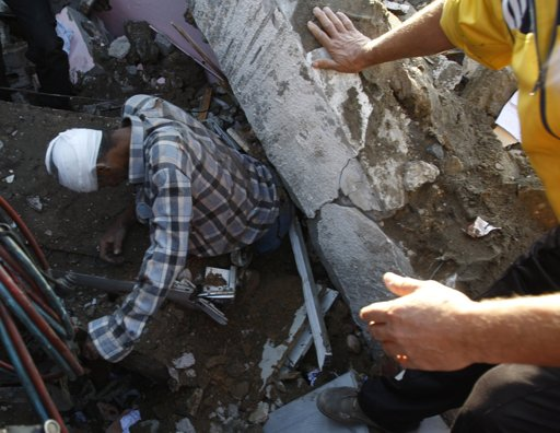 "wounded Palestinian man tries to get out from the rubble of his house after an Israeli air strike in Gaza City November 18, 2012. Israel bombed militant targets in Gaza for a fifth straight day on Sunday, launching aerial and naval attacks as its military prepared for a possible ground invasion, though Egypt saw ""some indications"" of a truce ahead. REUTERS/Ahmed Zakot"