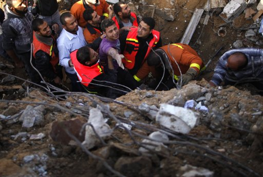 "Palestinian members of the Civil Defense help a survivor after he was pulled out from under the rubble of his destroyed house after an Israeli air strike in Gaza City November 18, 2012. Israel bombed militant targets in Gaza for a fifth straight day on Sunday, launching aerial and naval attacks as its military prepared for a possible ground invasion, though Egypt saw ""some indications"" of a truce ahead. REUTERS/Suhaib Salem"