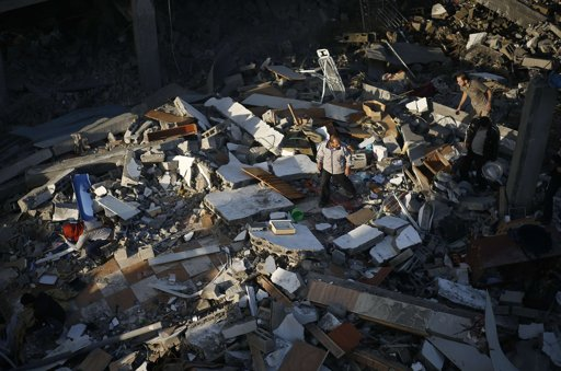 "Palestinians inspect as they walk amongst the rubble of a destroyed house after an Israeli air strike in the northern Gaza Strip November 18, 2012. Israel bombed militant targets in Gaza for a fifth straight day on Sunday, launching aerial and naval attacks as its military prepared for a possible ground invasion, though Egypt saw ""some indications"" of a truce ahead. REUTERS/Mohammed Salem"
