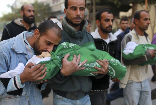 "A Palestinian man kisses the body of one of his children during their funeral in the northern Gaza Strip November 18, 2012. Two children Jumana Abu Sefan, 18 months old, and her brother Tamer, three and a half years old, were killed in an Israeli air strike on Sunday, hospital officials said. Israel bombed militant targets in Gaza for a fifth straight day on Sunday, launching aerial and naval attacks as its military prepared for a possible ground invasion, though Egypt saw ""some indications"" of a truce ahead. REUTERS/Mohammed Salem"