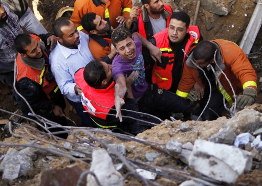 "Members of the Palestinian Civil Defense help a survivor after he was pulled out from under the rubble of his destroyed house after an Israeli air strike in Gaza City November 18, 2012. Israel bombed militant targets in Gaza for a fifth straight day on Sunday, launching aerial and naval attacks as its military prepared for a possible ground invasion, though Egypt saw ""some indications"" of a truce ahead. REUTERS/Suhaib Salem"
