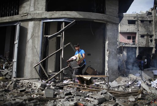 "A Palestinian carries his belongings after an Israeli air strike on a house in Gaza City November 18, 2012. Israel bombed militant targets in Gaza for a fifth straight day on Sunday, launching aerial and naval attacks as its military prepared for a possible ground invasion, though Egypt saw ""some indications"" of a truce ahead. REUTERS/Ahmed Jadallah"