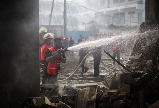 "Palestinian firefighters extinguish a fire after an Israeli air strike on a house in Gaza City November 18, 2012. Israel bombed militant targets in Gaza for a fifth straight day on Sunday, launching aerial and naval attacks as its military prepared for a possible ground invasion, though Egypt saw ""some indications"" of a truce ahead. REUTERS/Ahmed Jadallah"