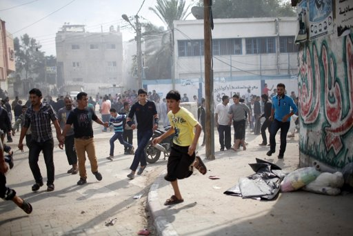 "Palestinians run after an Israeli air strike on a house in Gaza City November 18, 2012. Israel bombed militant targets in Gaza for a fifth straight day on Sunday, launching aerial and naval attacks as its military prepared for a possible ground invasion, though Egypt saw ""some indications"" of a truce ahead. REUTERS/Ahmed Jadallah"