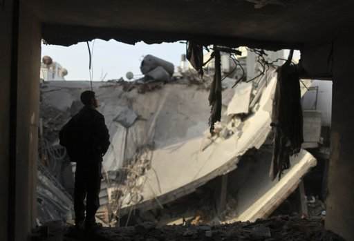 A Palestinian man looks at a destroyed house after an Israeli air strike in Gaza City November 19, 2012. Hostilities between Islamist militants and Israel entered a sixth day on Monday as diplomatic efforts were set to intensify to try to stop rocket fire from the Gaza Strip and Israeli air strikes on Gaza. International pressure for a ceasefire seemed certain to mount after the deadliest single incident in the flare-up on Sunday claimed the lives of at least 11 Palestinian civilians, including four children. REUTERS/Mohammed Salem (