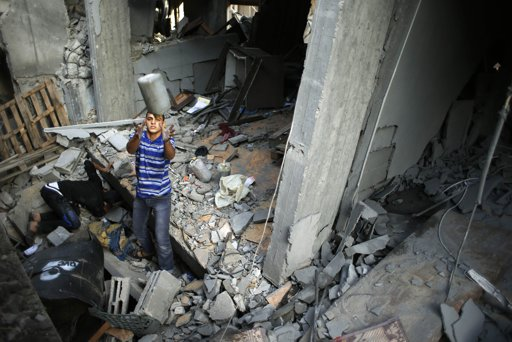 A Palestinian retrieves his belongings after an Israeli air strike on a house in Gaza City November 19, 2012. Hostilities between Islamist militants and Israel entered a sixth day on Monday as diplomatic efforts were set to intensify to try to stop rocket fire from the Gaza Strip and Israeli air strikes on Gaza. International pressure for a ceasefire seemed certain to mount after the deadliest single incident in the flare-up on Sunday claimed the lives of at least 11 Palestinian civilians, including four children. REUTERS/Mohammed Salem
