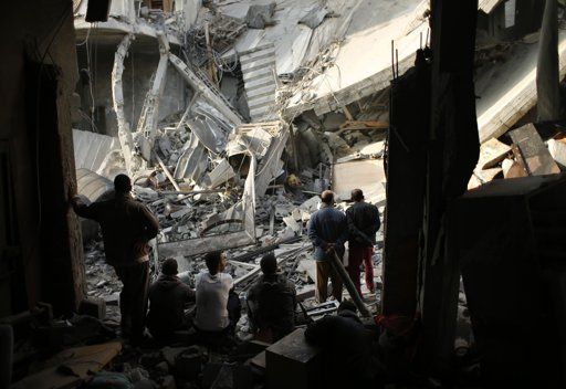 Palestinians look at a destroyed house after an Israeli air strike in Gaza City November 19, 2012. Hostilities between Islamist militants and Israel entered a sixth day on Monday as diplomatic efforts were set to intensify to try to stop rocket fire from the Gaza Strip and Israeli air strikes on Gaza. International pressure for a ceasefire seemed certain to mount after the deadliest single incident in the flare-up on Sunday claimed the lives of at least 11 Palestinian civilians, including four children. REUTERS/Mohammed Salem