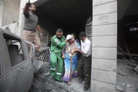 Palestinians help evacuate a wounded woman after an Israeli air strike in Gaza City November 19, 2012. REUTERS/Yasser Gdeeh