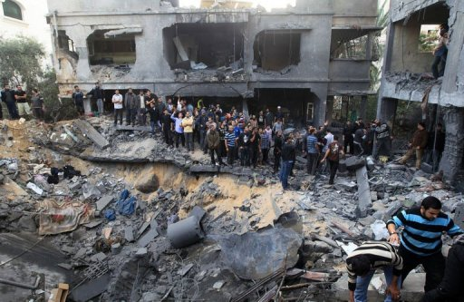 Palestinians gather around the destroyed home of the al-Dallu family following an Israeli air strike in Gaza City, on November 18, 2012. At least seven members of the same family, including four children, were among nine people killed when an Israeli missile struck a family home in Gaza City, the health ministry said  Photo Credit AFP