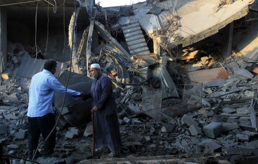 Palestinians walk past the debris of a destroyed home following an Israeli air strike in Gaza City, on November 19, 2012. An Israeli air strike early on Monday killed three Palestinians in a car in central Gaza, medics said, raising the toll to 85 as Israel's relentless air campaign entered its sixth day  Photo by AFP