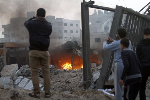 Palestinians take photographs of destruction after Israeli air strikes in Gaza City on November 19, 2012. An Israeli air strike early on Monday killed three Palestinians in a car in central Gaza, medics said, raising the toll to 85 as Israel's relentless air campaign entered its sixth day.