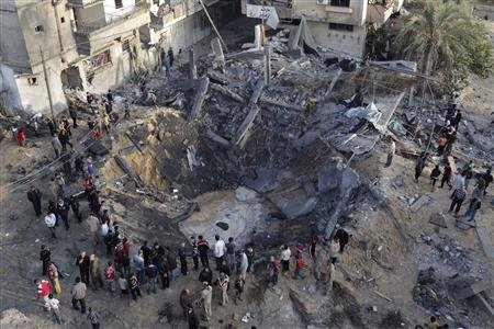 Palestinians gather around a destroyed house after an Israeli air strike in Khan Younis in the southern Gaza Strip November 19, 2012. REUTERS/Ibraheem Abu Mustafa