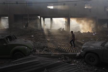 A Palestinian inspects the damage to a soccer stadium after an Israeli air strike in Gaza City November 19, 2012. REUTERS/Ahmed Zakot