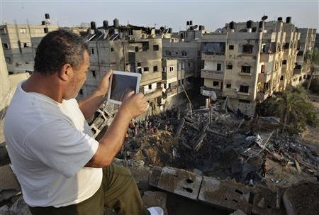 A Palestinian man uses his iPad as he takes pictures of a destroyed house after an Israeli air strike in Khan Younis in the southern Gaza Strip November 19, 2012. Israel bombed dozens of suspected guerrilla sites in the Hamas-ruled Gaza Strip on Monday and Palestinian rocket fire from the enclave dropped off as international efforts to broker a truce intensified. Ten civilians and two field commanders from the Islamic Jihad faction were killed and at least 30 other Palestinians were hurt in the new air strikes, hospital officials said, bringing the death toll from six days of clashes in Gaza to 85. REUTERS/Ibraheem Abu Mustafa