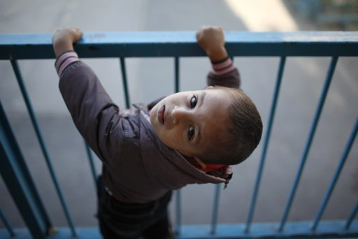 A displaced Palestinian boy, who fled his family's house, looks up as he stays with his family at a United Nations-run school in Gaza City November 20, 2012. From the sandy expanses of the northern Gaza Strip, Palestinian families are fleeing their homes destroyed by airstrikes, but refuse to blame the Hamas rocket crews who draw Israeli fire. REUTERS/Ahmed Jadallah