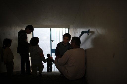 Displaced Palestinians, who fled their houses, gather at a staircase as they stay at a United Nations-run school in Gaza City November 20, 2012. From the sandy expanses of the northern Gaza Strip, Palestinian families are fleeing their homes destroyed by airstrikes, but refuse to blame the Hamas rocket crews who draw Israeli fire. REUTERS/Ahmed Jadallah