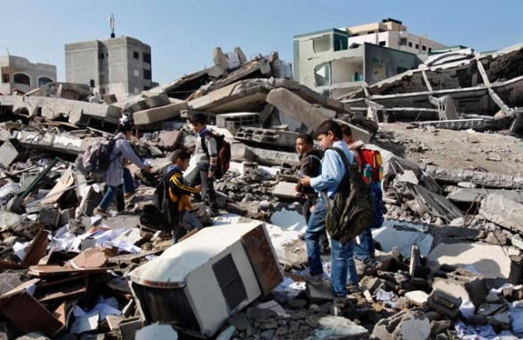 Palestinian schoolchildren walk in the rubble left days after an Israeli strike destroyed the Hamas interior ministry in Gaza City, Monday (AP photo)