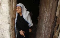 A Palestinian woman stands at the entrance to her house in the Shati refugee camp in Gaza City on November 2, 2012. Israel prevents nearly 7 million Palestinians scattered around the world from returning to their homes in Palestine, many of whom live in refugee camps in Lebanon, Jordan, the West Bank and Gaza.(Photo: AFP - Mohammed Abed)