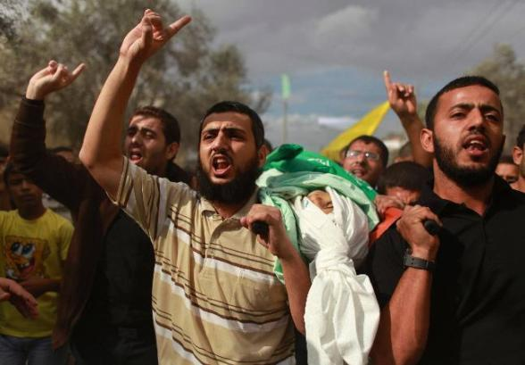 "Palestinians carry the body of Ahmed Abu Dagah, who was killed by gunfire from Israeli forces, during his funeral in Khan Younis in the southern Gaza Strip November 9, 2012. Gunfire from Israeli forces killed the Palestinian boy, Abu Dagah, in the Gaza Strip on Thursday, local medics said, during border clashes between the Israeli military and Palestinian militants. Israeli military officials said soldiers who were engaged in ""routine activity"" adjacent to the security fence came under attack from Palestinian militants and responded ""by firing at suspicious locations"". REUTERS/Mohammed Salem"