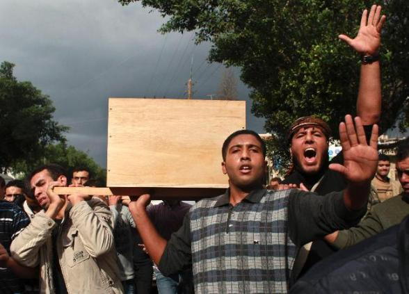 Palestinian carry the coffin of Mohammed Hararah, who was killed in Israeli shelling on Saturday, during his funeral in Gaza City November 11, 2012. Israel said it was poised to escalate attacks on the Gaza Strip on Sunday following a surge of rocket and mortar salvoes by Hamas and other factions in the Palestinian enclave. A missile strike wounded four Israeli troops on jeep patrol along the Gaza boundary on Saturday, triggering army shelling that killed four Palestinian civilians, one of them Hararah, and, in turn, dozens of short-range rocket launches out of Gaza that paralysed Israel's southern border towns. REUTERS/Mohammed Salem