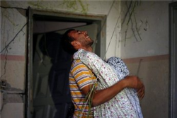 A Palestinian man hugs his mother after his house was damaged in an  Israeli airstrike in Gaza City Nov. 17, 2012. (Reuters/Mohamed Salem)