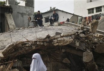 A woman walks past as policemen sit atop their destroyed  headquarters in Gaza City, Nov. 25. (Reuters/Mohammed Salem)