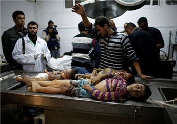 A Palestinian relative of four sibling children of the al-Dalou family,  who were killed in an Israeli air strike, reacts as he stands next their  bodies at a hospital in Gaza City November 18, 2012.  (Reuters/Mohammed Salem)