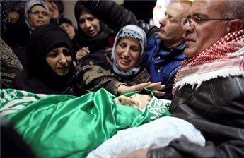 Relatives of Palestinian teenager Mohamad Salaymeh mourn next to his  body during his funeral in the West Bank city of Hebron,  Dec. 13, 2012. (Reuters/Ammar Awad)