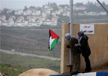 A protester holds the Palestinian flag with the Jewish settlement of Halamish seen in the background during clashes between stone-throwing  protesters and Israeli soldiers in Nabi Saleh, near Ramallah on Dec. 21. (Reuters/Mohamad Torokman)