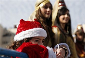 A girl watches a Christmas parade outside the Church of Nativity in Bethlehem on Dec. 24. (Reuters/Darren Whiteside)